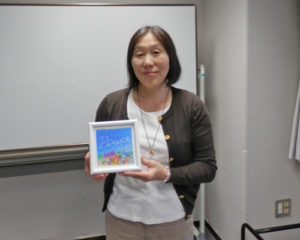 自作のアートと一緒に写る堀内祐子先生