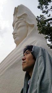 作者 近藤健が大船観音を背景に観音様と同じポーズをとっている写真