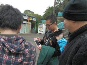 野毛山動物園でスマホを見せ合う2人