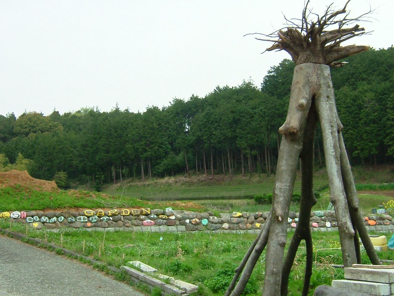 ユニークなオブジェ越しの新たに開墾している畑