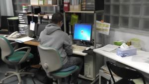不登校新聞を編集する石井さんを後ろから撮影