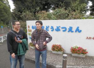 動物園の看板の前で話す2人