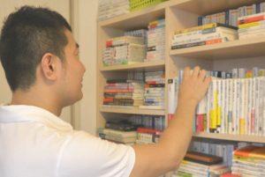 本棚に手の伸ばす関水さん
